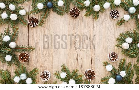 Christmas frame out of fir tree twigs pine cones baubles christmas balls and glitter balls on brown wooden background with lots of copy space.