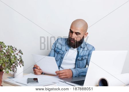 A Serious Bald Businessman With Thick Black Beard And Mustache Wearing Jean Shirt Being Busy With Do