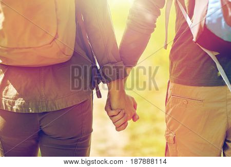 travel, hiking, backpacking, tourism and people concept - close up of couple with backpacks holding hands and walking along country road