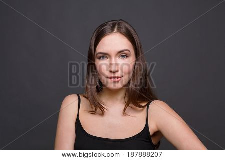 Hesitation. Doubtful young woman on dark background.