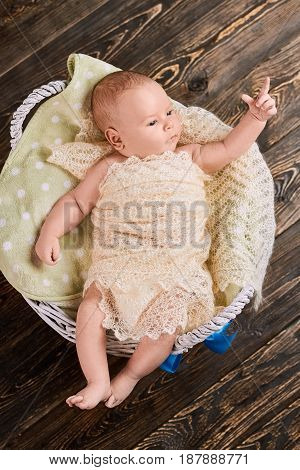 Little kid pointing finger. Child in basket, top view. Baby sign language.