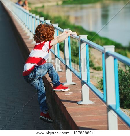 photo of little boy climbing over the fence