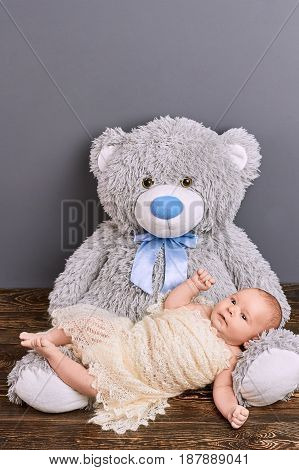 Infant and teddy bear. Cute child wrapped in shawl.