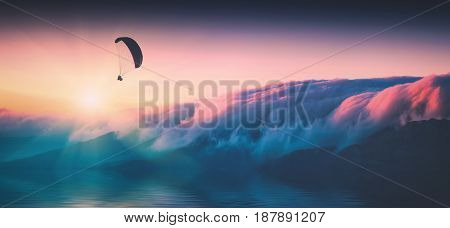 Paraglide silhouette in a light of sunrise above the island covered with pink morning clouds. Instagram stylization.