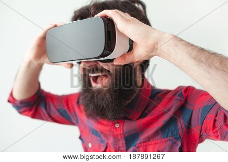 Laughing man adjusting the goggles during the virtual reality experience.
