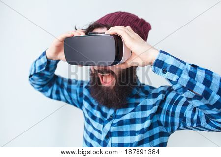 Excited bearded man adjusting the virtual reality headset on his head. Horizontal studio shot.