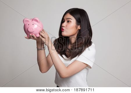 Young Asian Woman Kiss  A Pink Coin Bank.