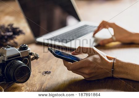 Person Using Laptop And Smartphone At Workspace With Vintage Photo Camera