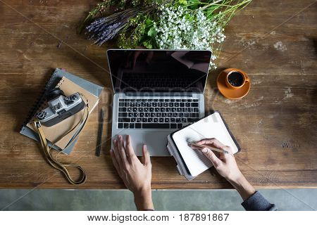 Person Using Laptop And Graphic Tablet At Workspace With Notebooks And Vintage Camera