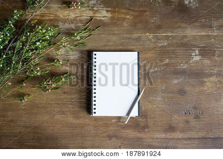 top view of notepad with pencil and flowers on wooden tabletop