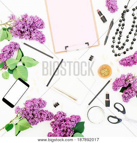 Freelancer or blogger desk workspace with clipboard, mobile phone, notebook, lipstick, lilac and accessories on white background. Flat lay, top view. Beauty blog concept.