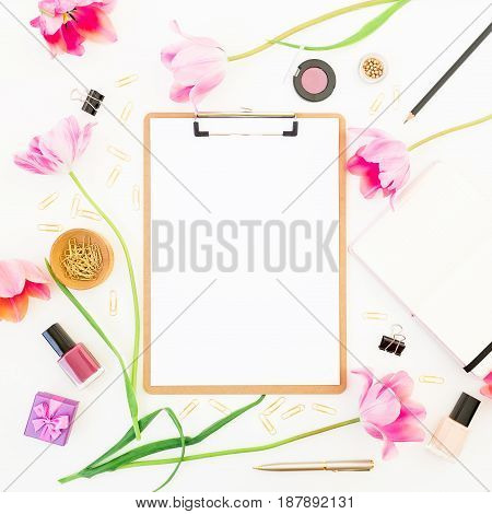 Freelancer or blogger workspace with clipboard, notebook, cosmetics, tulip and accessories on white background. Beauty blog concept. Flat lay, top view.