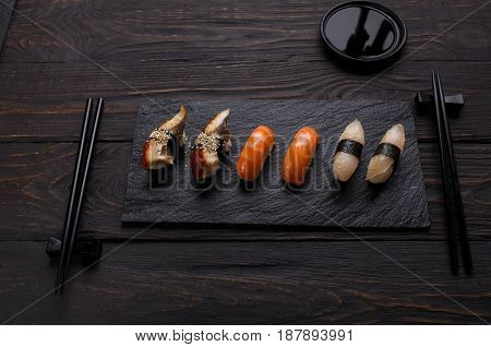 Colorful sushi and rolls platter in japanese restaurant, with chopsticks and soy sauce on dark background