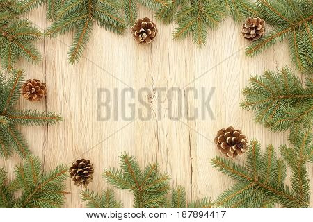 Christmas frame out of fir tree twigs and pine cones on brown wooden background with lots of copy space.