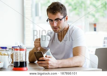Portrait of handsome young man using his mobile phone while enjoying the breakfast in the kitchen.