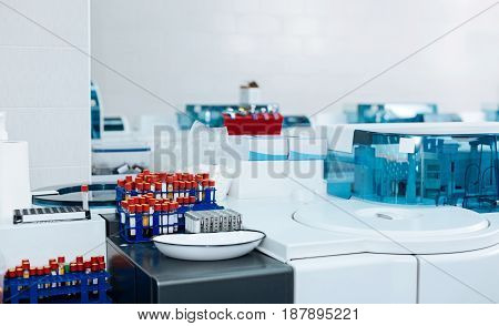 Sterile workplace. Big holders for test tubes with blood standing at every table, lab is very convenient and clean