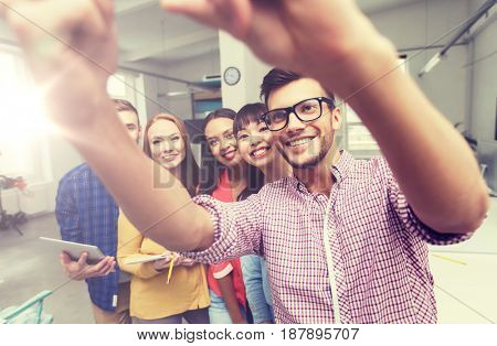 business, technology, startup and people concept - happy international creative business team taking selfie at office