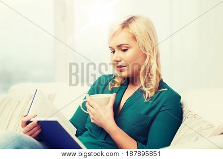 leisure, literature and people concept - young woman with tea cup reading book at home