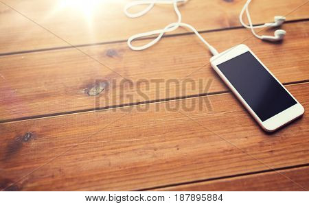 technology, music, gadget and object concept - close up of white smartphone and earphones on wooden surface with copy space