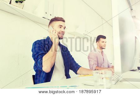 business, technology, education and people concept - happy young creative man or student with computer at office calling on smartphone