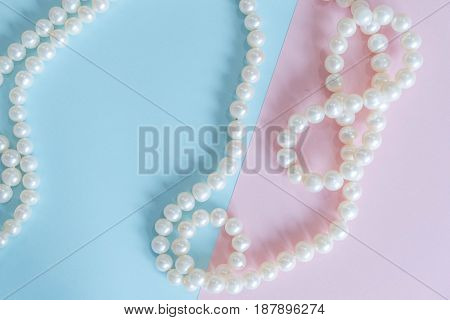 Pearls necklaces Women's Accessories. glamorous background. blue and pink paper