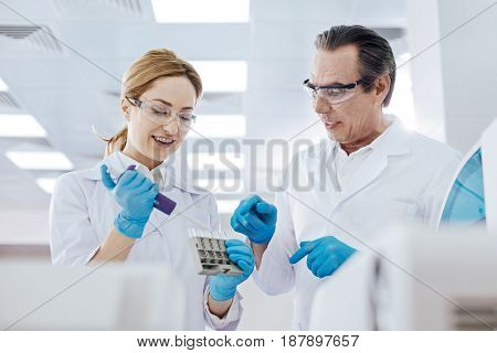 Two coworkers. Positive lab assistant wearing protective glasses and holding medicine dropper in right hand while keeping smile on face