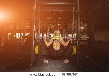 Woman exercising with barbell in fitness class. Female workout in gym with barbell.