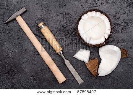 Top View Of Broken Coconut With Hammer And Chisel On Black