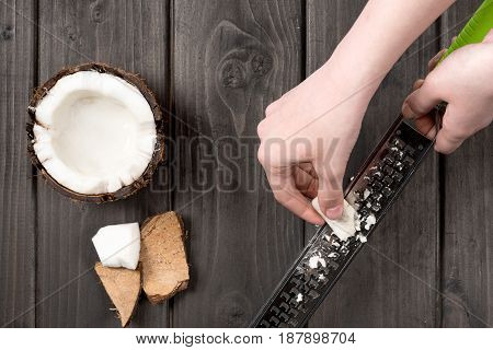 Human Hands Slashing Coconut Pieces With Grater On Wooden Background, Coconut Shavings