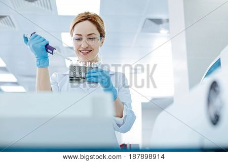 Take some drops. Pretty woman in rubber gloves holding medicine dropper in left hand while looking downwards and keeping smile on face