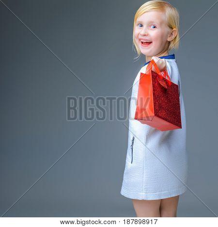 Smiling Modern Girl On Grey With Red Christmas Shopping Bag