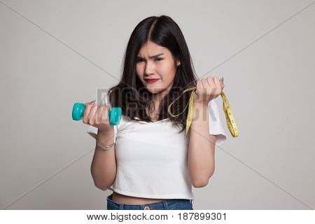 Exhausted  Asian Woman With Dumbbells And Measuring Tape.