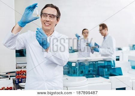 Do not shake it. Handsome kind practitioner keeping smile on his face raising arms while holding test tube in right hand