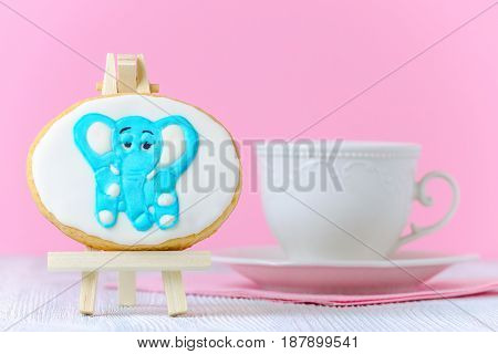 homemade children's cookie with a elephant on the painting easel and a cup of milk or tea on pink background, copy space
