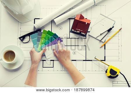 business, architecture, building, construction and people concept - close up of designer hands with color palette and house blueprint
