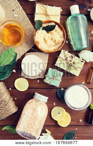 beauty, spa, therapy, natural cosmetics and wellness concept - close up of body care cosmetic products on wood