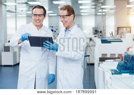 Always smile. Competent technicians wearing protective glasses looking at screen of tablet while feeling happiness