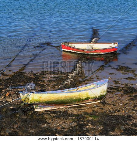 Two old rowing boats red and yellow at low tide in a river estuary blue water