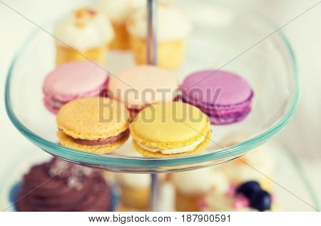 unhealthy eating, sweets, dessert, baking and junk food concept - close up of cake stand with macaroon cookies
