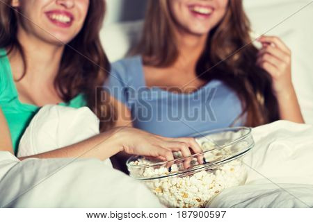 friendship, people, pajama party, entertainment and junk food concept - close up of happy friends or teenage girls eating popcorn and watching movie or tv series at home