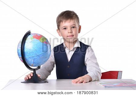 Schoolboy at the desk holding a globe of world isolated on white background