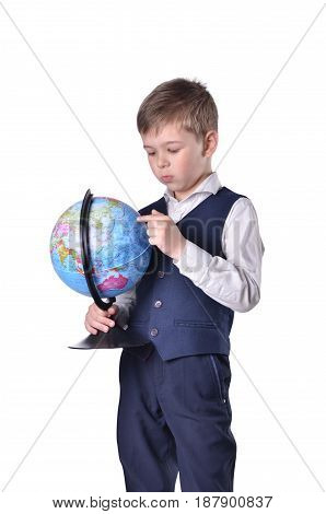 Standing schoolboy hold a globe of world and searching something on it isolated on white backgroudn