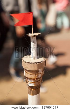Cardboard handmade ship mast with a red flag on top. Carton lighthouse miniature model painted in white. Child crafted creative fun toy
