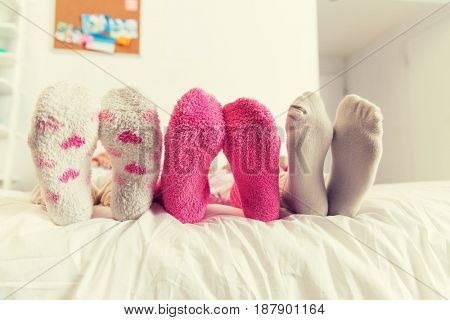 friendship, people and pajama party concept - close up of women feet in socks on bed at home