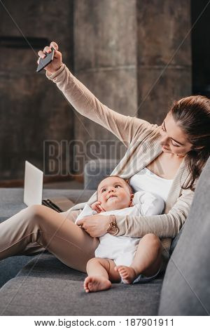 Happy Mother With Her Little Son Taking Selfie On Smartphone