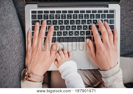 Cropped shot of woman's hands with hand of her son lying on laptop's keyboard