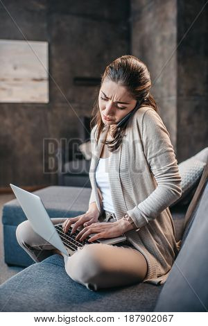 Serious Woman Having Conversation On Smartphone And Typing On Laptop At Home. Woman During Work At H