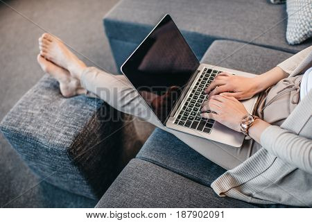 Cropped Shot Of Woman Typing On Laptop While Sitting On The Couch At Home