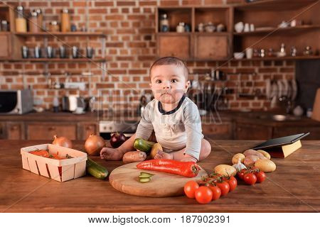 Little Boy With Variety Of Raw Vegetables Sitting On Kitchen Table