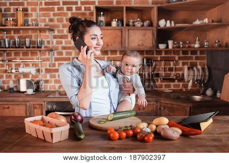 Young Mother Holding Her Son On Arms And Talking On Smartphone During Dinner Preparation In The Kitc